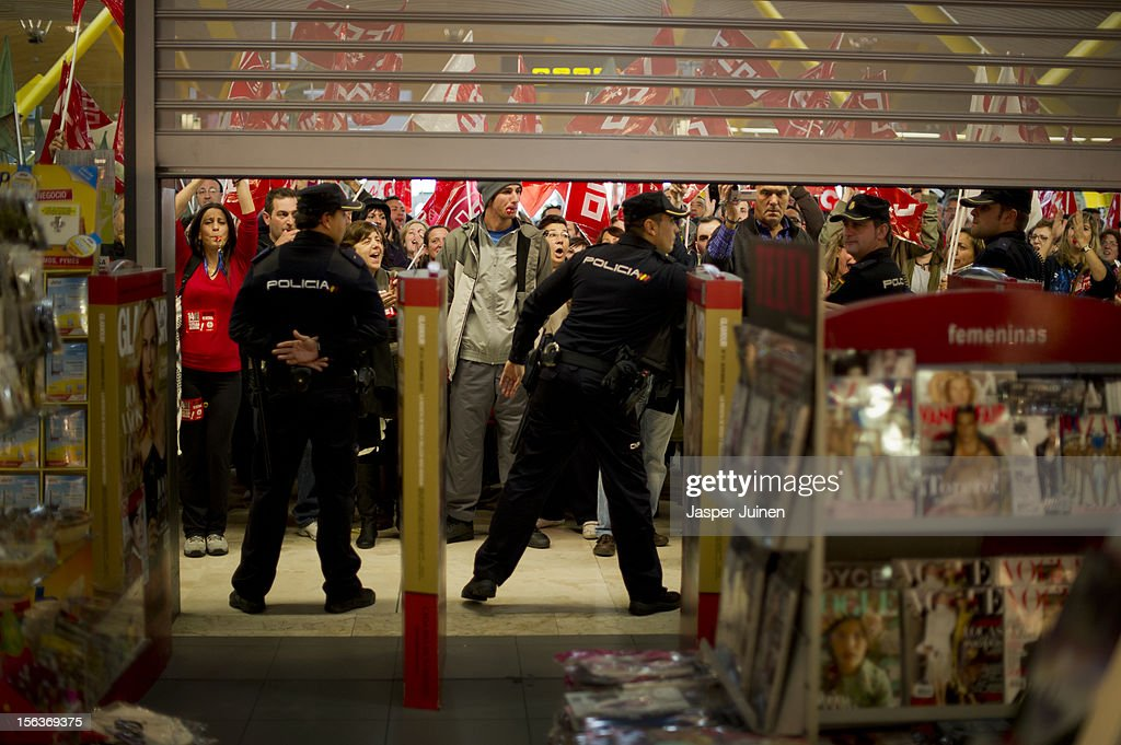 Demonstrators shout slogans in front of a shop, forcing it to close for business, as staff lower the shops window shutters at Barajas airport on November 14, 2012 in Madrid, Spain. A coordinated general strike by unions in Spain and Portugal has paralysed public transport in the two countries with further strikes planned across Europe. The strike against the governments' austerity measures have force hundreds of flights to be cancelled and factories and ports to come to a standstill.