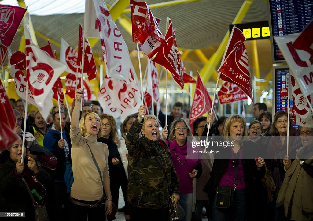 Demonstrators shout slogans in front of a shop, forcing it to close for business, at Barajas airport on November 14, 2012 in Madrid, Spain. A coordinated general strike by unions in Spain and Portugal has paralysed public transport in the two countries with further strikes planned across Europe. The strike against the governments' austerity measures have force hundreds of flights to be cancelled and factories and ports to come to a standstill.