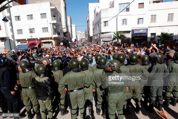 Demonstrators shout slogans in front of Moroccan security forces during a march in defiance of a government ban in the northern Moroccan city of...