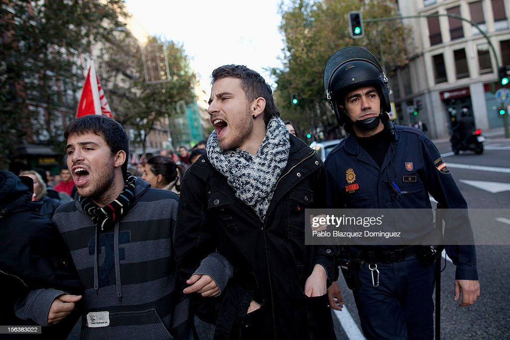 Demonstrators shout slogans next to a riot police officer on November 14, 2012 in Madrid, Spain. A coordinated general strike by unions in Spain and Portugal has paralysed public transport in the two countries with further strikes planned across Europe. The strike against the governments' austerity measures have force hundreds of flights to be cancelled and factories and ports to come to a standstill.