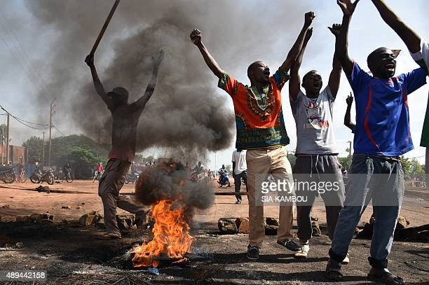 Demonstrators shout slogans next to burning tyres in the Tampouy neighbourhood of Ouagadougou during a protest against a regional proposal to end the...