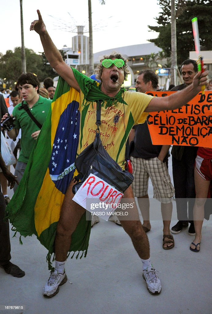 Demonstrators shout slogans outside the Mario Filho --Maracana-- stadium during a protest against Maracana's privatization and the demolition of the former Indigenous Museum, at the time that a test event is taking place inside, in Rio de Janeiro on April 27, 2013. The Maracana will host the upcomig Confederations Cup --next June--, the Brazil 2014 FIFA World Cup and the 2016 Summer Olympics.
