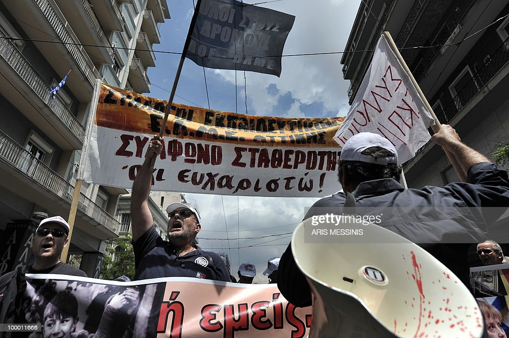 Demonstrators shout slogans prior to a protest march marking the 24-hour general strike against the austerity measures in central Athens on May 20, 2010. Thousands of protesters took to the streets of Athens and second city Thessaloniki in a new general strike against the government's debt-dictated austerity spending cuts and pension reforms during a general strike on May 20, 2010. The banner in the background reads ' Stability pact? No thank you '.