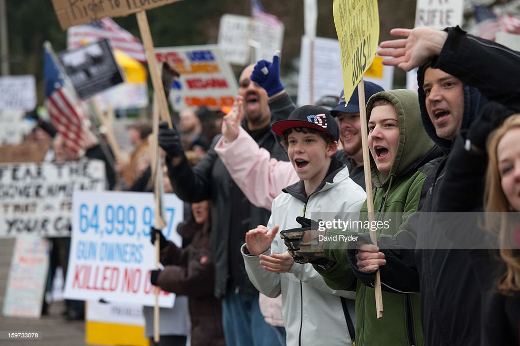 Demonstrators shout to passing cars during a progun rally on January 19 2013 in Olympia Washington The Guns Across America national campaign drew...