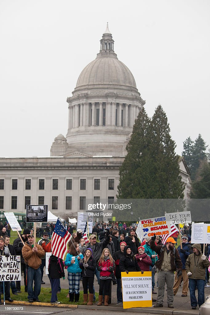Demonstrators shout to passing cars in front of the capitol building during a pro-gun rally on January 19, 2013 in Olympia, Washington. The Guns Across America national campaign drew thousands of protesters to state capitols, including over 1,000 in Olympia.
