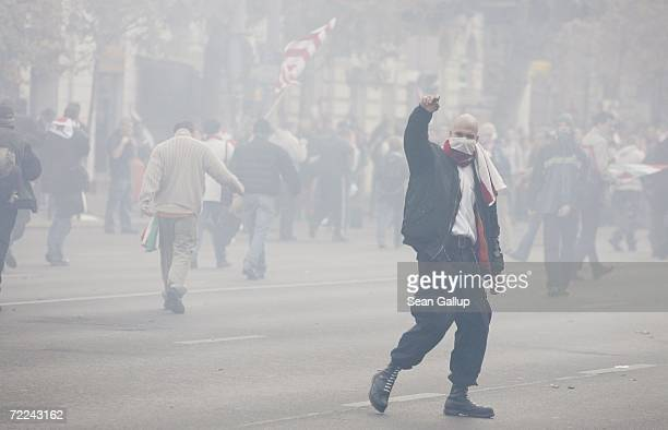 Demonstrators shrouded in tear gas flee police during violent street protests October 23 2006 in Budapest Hungary The country is officially...