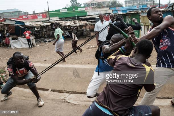 TOPSHOT Demonstrators simulate throwing a stone toward police station on October 16 2017 in Kisumu to demand the removal of officials from national...