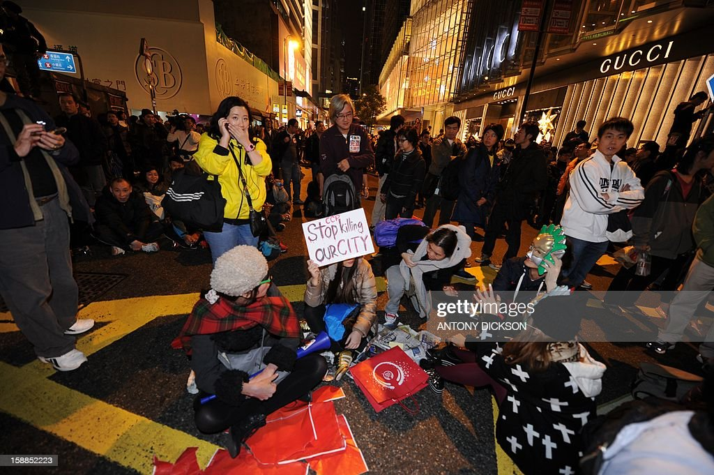 Demonstrators sit on a main road running thru the central business district during a sit in protest against the city's leader Leung Chun-ying in Hong Kong on January 1, 2013. Tens of thousands of protesters took to the streets of Hong Kong on January 1, calling for the city's embattled leader to quit and demanding greater democracy 15 years after it returned to Chinese rule.