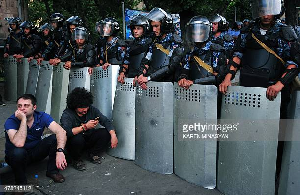 Demonstrators sit on a street in front of a line of riot police during a protest against an increase of electricity prices in the Armenian capital...