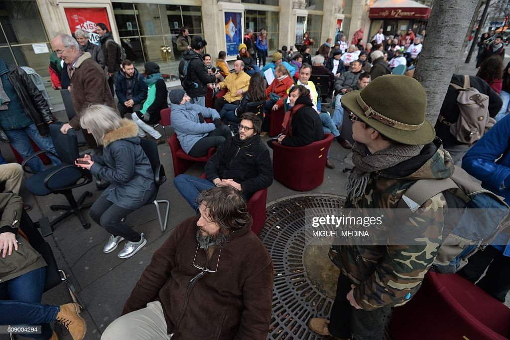 Demonstrators sit on chairs taken from bank offices on February 8, 2016 in the place du Chatelet in Paris during a demonstration against bank system and tax fraud, as former French budget minister Jerome Cahuzac goes on trial on February 8 for tax fraud. Cahuzac resigned in disgrace in 2013 after admitting to having a secret Swiss bank account, and faces up to seven years in jail and two million euros ($2.2 million) in fines. AFP PHOTO / MIGUEL MEDINA / AFP / MIGUEL MEDINA