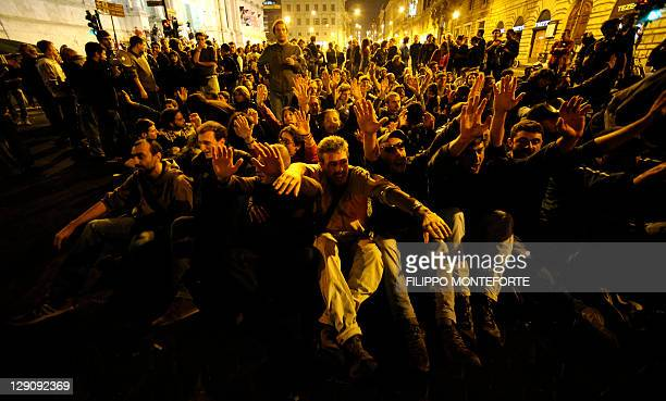 Demonstrators sit on the street as they take part in a protest against the Bank of Italy in the centre of Rome on October 13 2011 after President of...