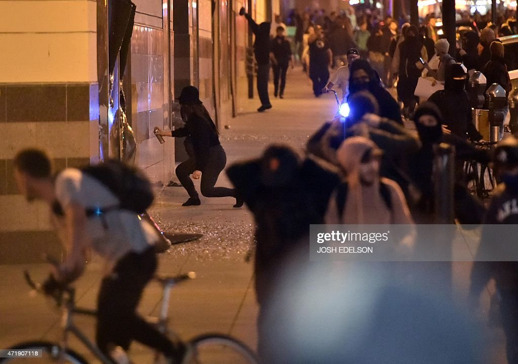 Demonstrators spray paint on a wall during a May Day protest in Oakland California on May 1 2015 Hundreds marched throughout the city vandalizing...