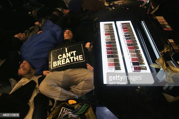 Demonstrators stage a 'diein' next to a lipstick display inside the iconic Macy's department store in Midtown Manhattan on December 5 2014 in New...