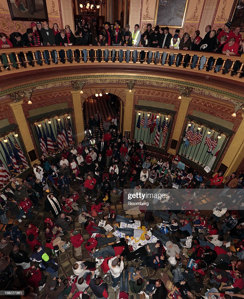 Demonstrators stage a sit-in in the rotunda of the Capitol in Lansing, Michigan, U.S., on Tuesday, Dec. 11, 2012. Michigan lawmakers approved bills to prohibit mandatory union dues in workplaces as thousands of chanting protesters thronged the Capitol. Photographer: Jeff Kowalsky/Bloomberg via Getty Images