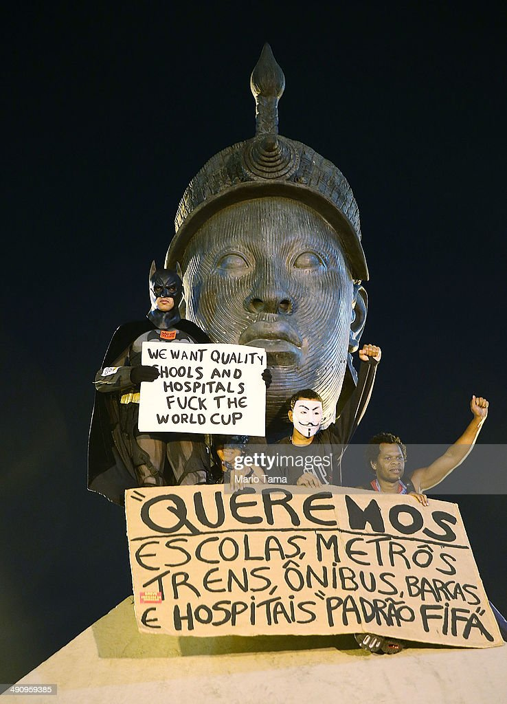 Demonstrators stand atop a monument honoring Afro-Brazilian hero Zumbi dos Palmares at a protest against the upcoming 2014 World Cup on May 15, 2014 in Rio de Janeiro, Brazil. Anti-World Cup demonstrations were held across the country today.