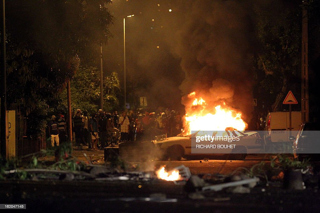 Demonstrators stand behind a burning car as they face riot police in the city of Le port, west of the French island of La Reunion, on February 18, 2013, on the sideline of a demonstration to demand government-subsidized contracts. The demonstrators blocked in the morning the main road between the north and the south of the island but after one hour of riot later in the day, the traffic start again without any injuries. AFP PHOTO / RICHARD BOUHET