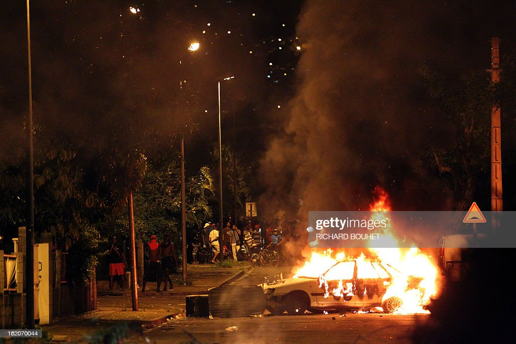 Demonstrators stand behind a burning car as they face riot police in the city of Le port, west of the French island of La Reunion, on February 18, 2013, on the sideline of a demonstration to demand government-subsidized contracts. The demonstrators blocked in the morning the main road between the north and the south of the island but after one hour of riot later in the day, the traffic start again without any injuries.