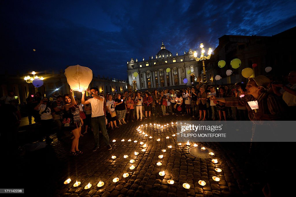 Demonstrators stand by candels shaping a heart and the number 30 as they coomemorate the 30th anniversary of Emanuela Orlandi disappearance in Saint Peter's Square at the Vatican on June 22, 2013. Fifteen-year-old Emanuela Orlandi, the daughter of a Vatican messenger who lived with his family in Vatican City, disappeared on June 22, 1983 when she went to a music lesson. The still unsolved Orlandi saw over the years a number of theories regarding the motives for the crime from claimes that the kidnapping was done by extremist Muslim terrorists to demand the release of Mehmet Ali Agca from prison after he shot pope John Paul II to latest exorcist Gabriele Amorth claiming that she was kidnapped by a member of the Vatican police for sex parties, and then murdered. AFP PHOTO/ Filippo MONTEFORTE