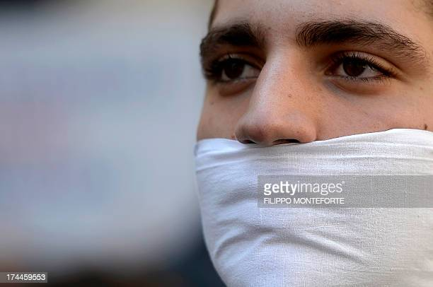 Demonstrators stand in front of the Italian parliament with mouth and hands tied to protest against homophobia in Rome's Piazza Montecitorio on July...