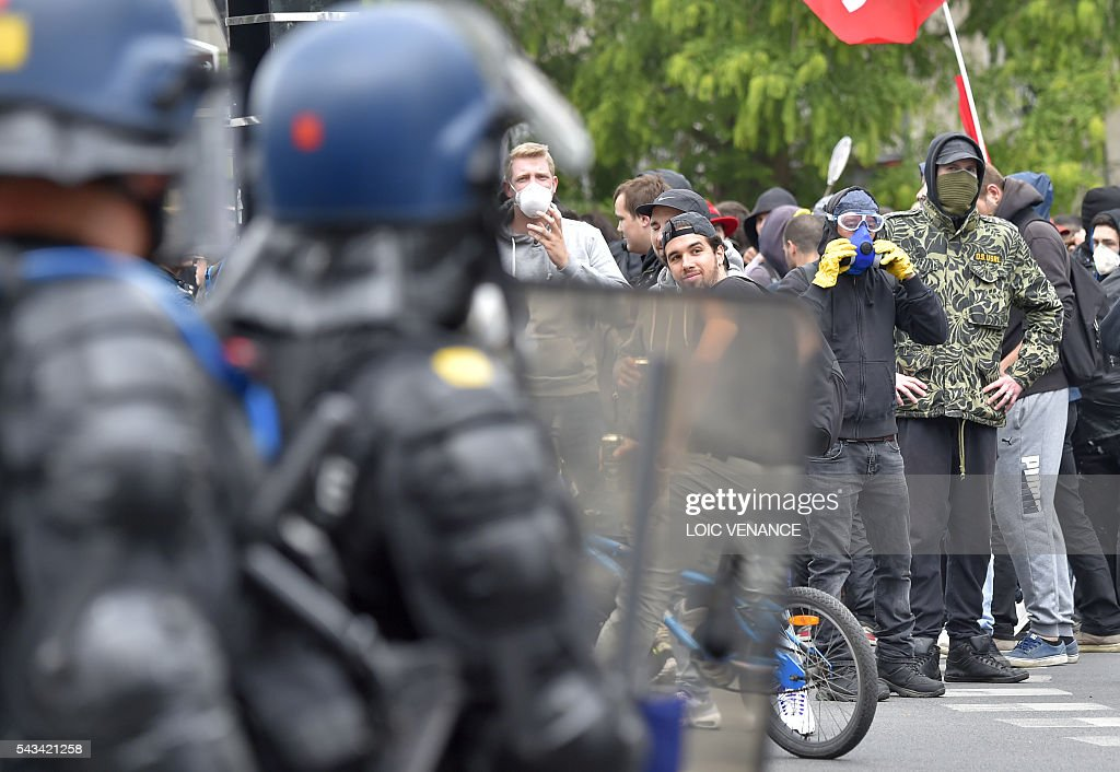 Demonstrators stand next to French riot police during a protest against controversial labour reforms, on June 28, 2016 in Nantes, western France. People took to the streets in France on June 28 in the latest protest march in a marathon campaign against the French Socialist government's job market reforms. Last month the government used a constitutional manoeuvre to push the bill through the lower house without a vote in the face of opposition from Socialist backbenchers. / AFP / LOIC