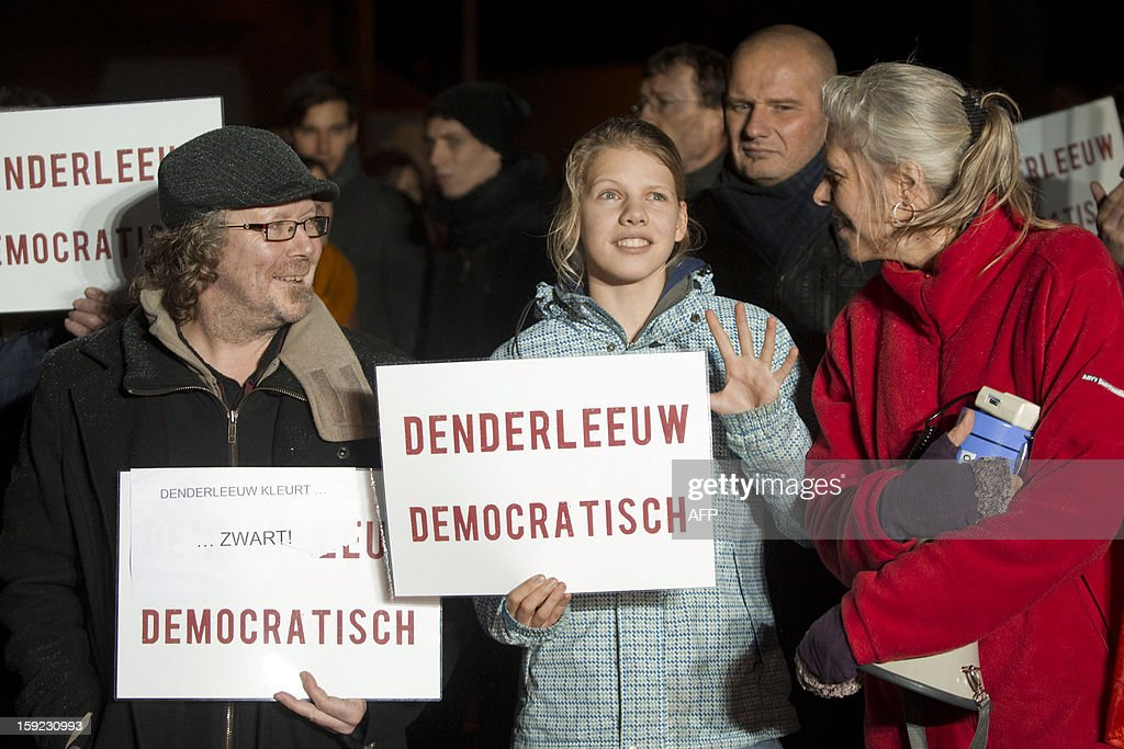 Demonstrators stand with placards reading 'Denderleeuw democratic' and 'The colour of Denderleeuw is black) during a protest outside the city hall prior to the installation of the new municipal council in Denderleeuw late on January 9, 2013. THE CD&V and N-VA parties agreed to form a minority coalition but will receive support from Flemish far-right party Vlaams Belang. By making this agreement the coalition is breaking the 'cordon sanitaire' agreement to not work with the Vlaams Belang party. AFP PHOTO / BELGA -KRISTOF VAN ACCOM