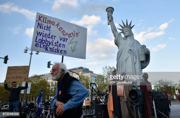 Demonstrators standing next to a mockup of the Statue of Liberty hold up a poster reading 'Climate Chancellor Don't cave in again in front of...