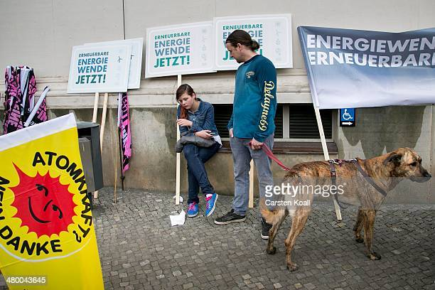 Demonstrators stay on the side while other demonstrators march to demand a faster transition to renewable energy sources on March 22 2014 in Postdam...
