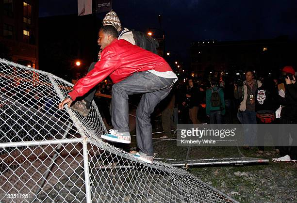 Demonstrators stomp on a chain link fence they pulled down November 19 2011 in Oakland California Occupy Oakland protesters calling for a 'mass day...