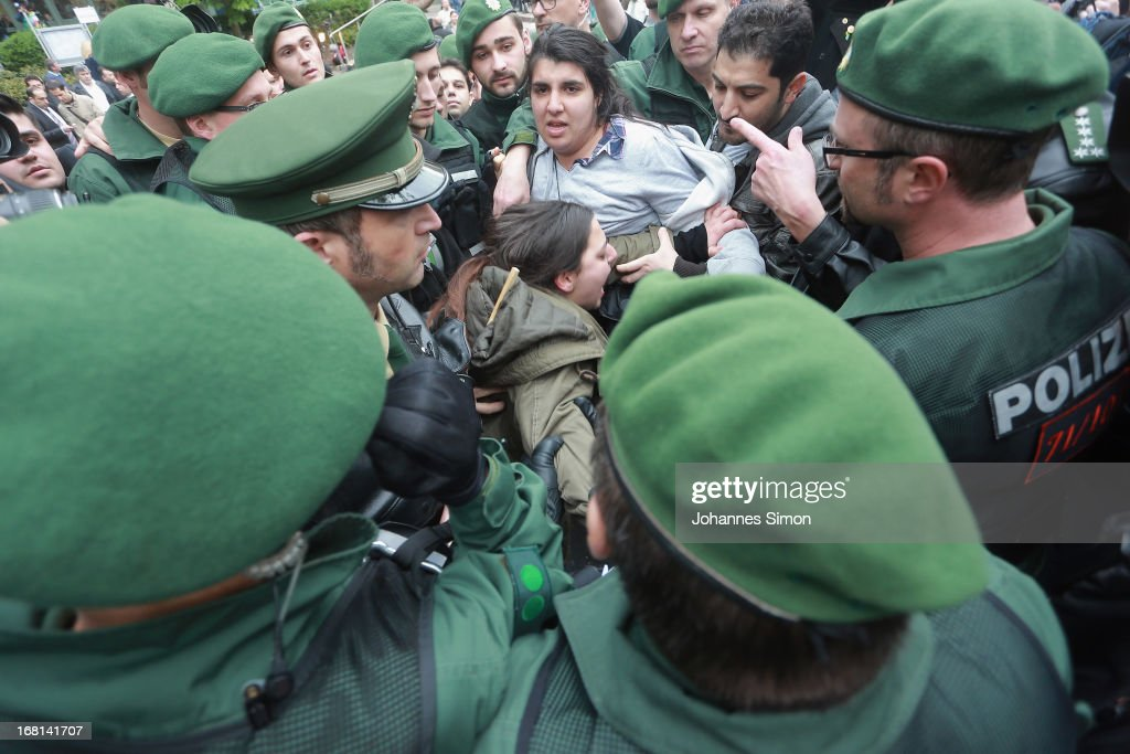 Demonstrators struggle with riot police men outside the entrance to the courtroom at the Oberlandesgericht Muenchen court building on the first day of the NSU neo-Nazi murder trial on May 6, 2013 in Munich, Germany. The main defendant, Beate Zschaepe, is on trial for her role in assisting Uwe Boehnhardt and Uwe Mundlos in the murder of nine immigrants and one policewoman across Germany between 2000 and 2007, and four other co-defendants, including Ralf Wohlleben, Holder G., Carsten S. and Andre E., are accused of assisting the trio. Zschaepe, Mundlos and Boehnhardt lived together for years undetected by police and called themselves the National Socialist Underground, or NSU. The case only came to light after Mundlos and Boehnhardt committed suicide after the two were cornered by police following a bank robbery in 2011.