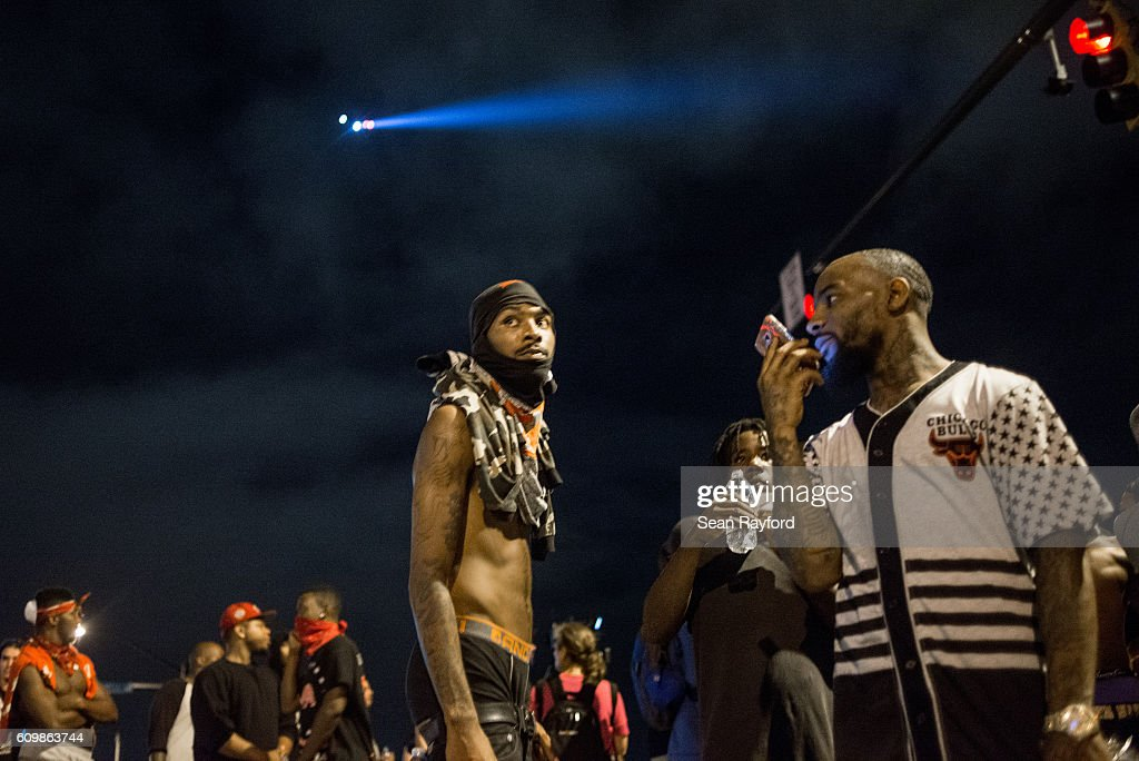Demonstrators take a break from marching as a helicopter flies above on September 23, 2016 in Charlotte, NC. Protests began on Tuesday night following the fatal shooting of 43-year-old Keith Lamont Scott at an apartment complex near UNC Charlotte. A state of emergency was declared overnight in Charlotte and a midnight curfew was imposed by mayor Jennifer Roberts, to be lifted at 6 a.m. Despite a midnight curfew, police allowed the peaceful march to continue without interference.