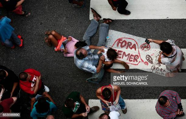 Demonstrators take a rest as they take part of a protest during a national strike against the government's social welfare reform bill which seeks to...
