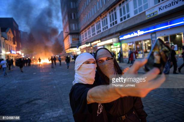 Demonstrators take a selfie photo with a burning crush barrier in the background during a demonstration against the G20 Summit on July 7 2017 in...