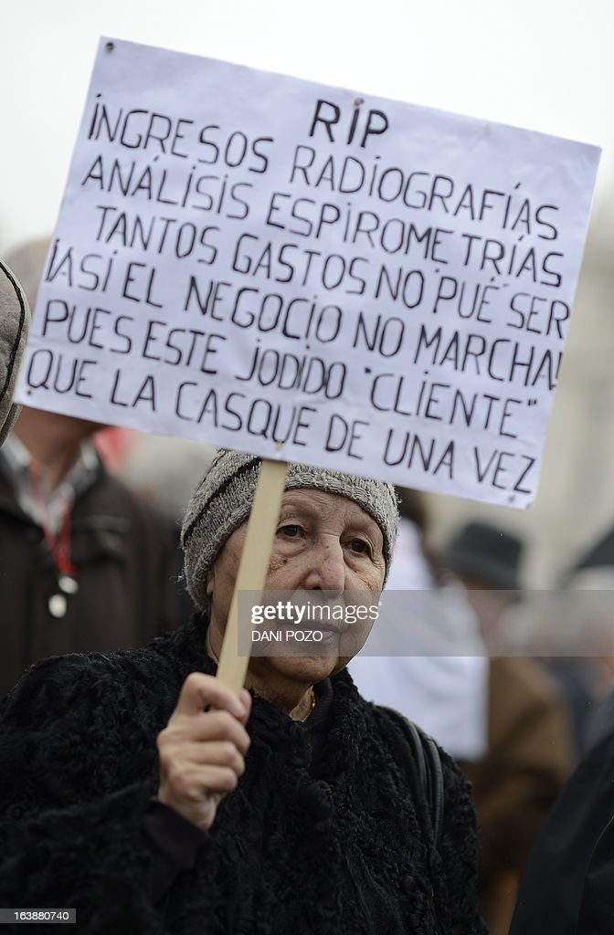 Demonstrators take part in a protest against government's austerity measures and health care spending cuts in Madrid on March 17, 2013. The placard reads: 'RIP. Admissions, radiographs, analysis, spirometry. so many expenses could not have been run up unless the business was not good. This 'client' should die soon.' AFP PHOTO / DANI POZO