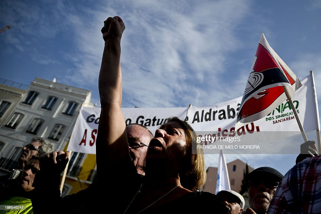 Demonstrators take part in a protest called by the main workers union CGTP against the 2014 State Budget in front of the Portuguese Parliament in Lisbon on November 1, 2013. Thousands of demonstrators protested in Portugal today against salary cuts and public sector reforms planned in the government's 2014 budget under the country's international bailout deal. After nearly three years of belt-tightening, the budget aims to save a further 3.9 billion euros (5.3 billion USD), partly through cutting public sector salaries and pensions.