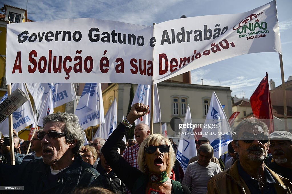 Demonstrators take part in a protest called by the main workers union CGTP against the 2014 State Budget in front of the Portuguese Parliament in Lisbon on November 1, 2013. Thousands of demonstrators protested in Portugal today against salary cuts and public sector reforms planned in the government's 2014 budget under the country's international bailout deal. After nearly three years of belt-tightening, the budget aims to save a further 3.9 billion euros (5.3 billion USD), partly through cutting public sector salaries and pensions. The banner reads: 'Thieving and lying Government, the solution is to resign' AFP PHOTO / PATRICIA DE MELO MOREIRA