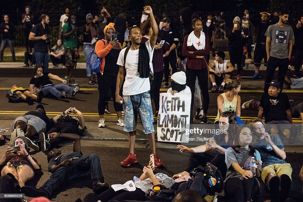Demonstrators take part in a protest on September 22, 2016 in Charlotte, NC. Protests began on Tuesday night following the fatal shooting of 43-year-old Keith Lamont Scott at an apartment complex near UNC Charlotte. A state of emergency was declared overnight in Charlotte and a midnight curfew was imposed by mayor Jennifer Roberts, to be lifted at 6 a.m.