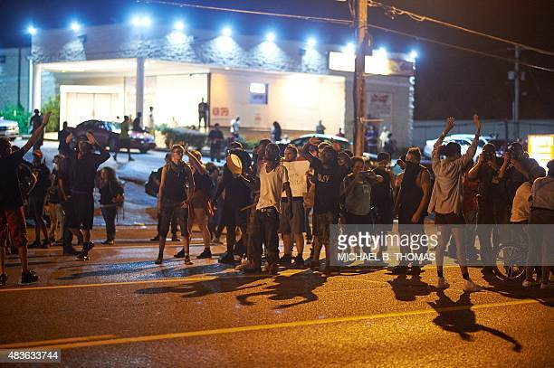 Demonstrators take to the streets during a civil disobedience action on August 10 2015 on West Florissant Avenue in Ferguson Missouri The night ended...