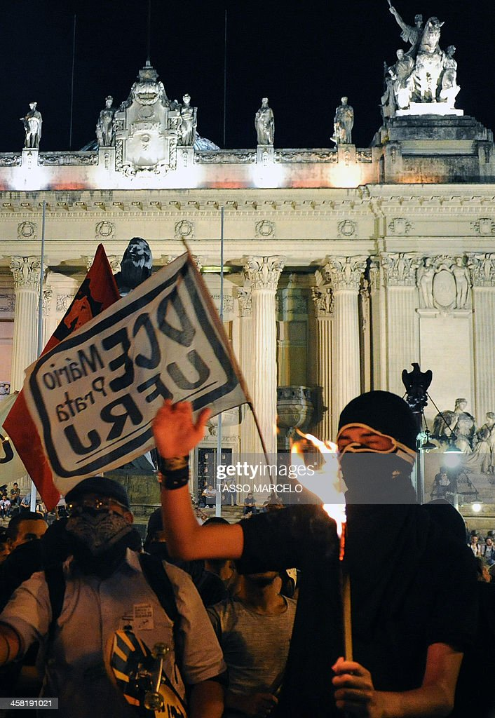 Demonstrators takes part in a protest against a public transport fare hike announced for January 2014 by Rio de Janeiro's Mayor Eduardo Paes, in front of the Municipal Theatre in Rio, Brazil, on December 20, 2013. AFP PHOTO/TASSO MARCELO