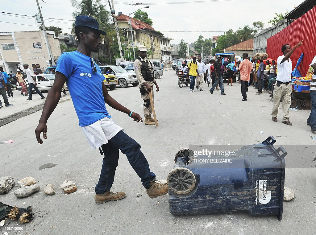 Demonstrators throw items into the street to create a barricade May 14 2013 in Port-au-Prince, Haiti a a police officer(C) looks on. Demonstraters were protesting the cost of living. AFP PHOTO / Thony BELIZAIRE