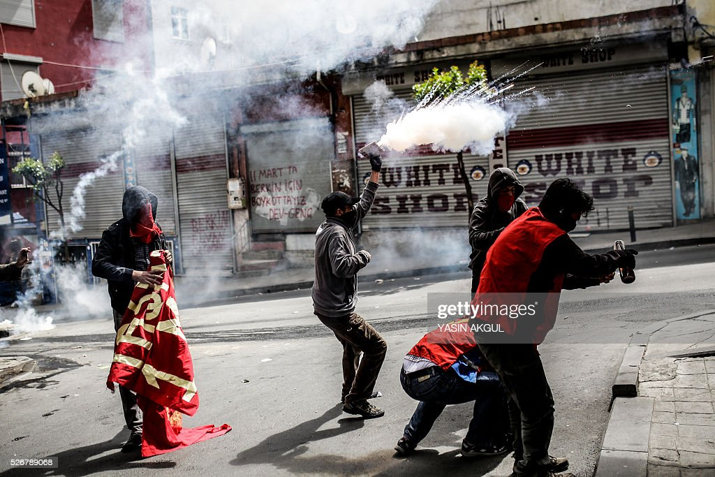 Demonstrators throw molotov cocktails and shoot firecrackers during a May Day rally in the Okmeydani neighbourhood of Istanbul on May 1, 2016. Turkish police clamped down on unauthorised protests during a tense May Day in Istanbul, using tear gas and water cannon against demonstrators and imposing a heavy security blanket on the city. / AFP / YASIN