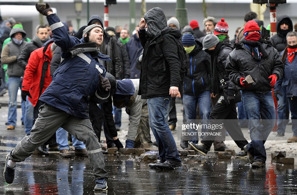 Demonstrators throw stones at riot police during a demonstration of workers of ArcelorMittal on the sideline of a meeting between the Federal Government, the Walloon Government and ArcelorMittal unions, on January 25, 2013 near the Prime Minister's residence in Brussels. Yesterday steelmaker ArcelorMittal announced the closure of the cold lines in Liege. 1300 jobs are threatened.