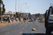 Demonstrators throw stones to Armored vehicle during a protest prior to municipal elections in Meyerton town of Guaeteng South Africa on July 22 2016