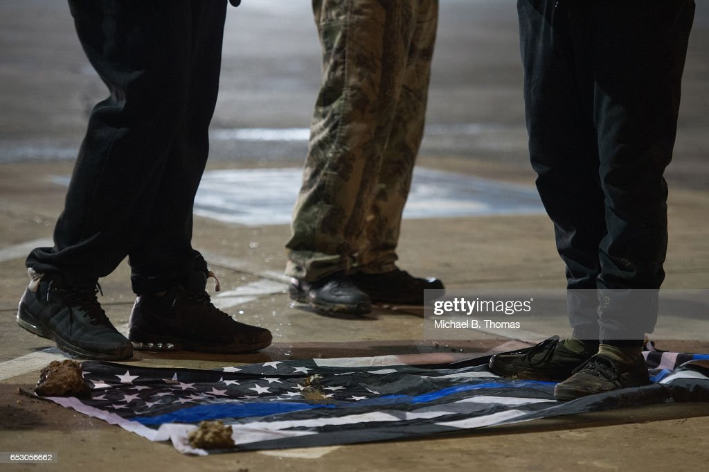 Demonstrators trample on an American flag that symbolizes support for law enforcement as they protests outside the Ferguson Market and Liquor on March 13, 2017 in Ferguson, Missouri. Tension and protest in Ferguson has arisen in response to video footage of slain 18 year-old Michael Brown in a recent documentary.