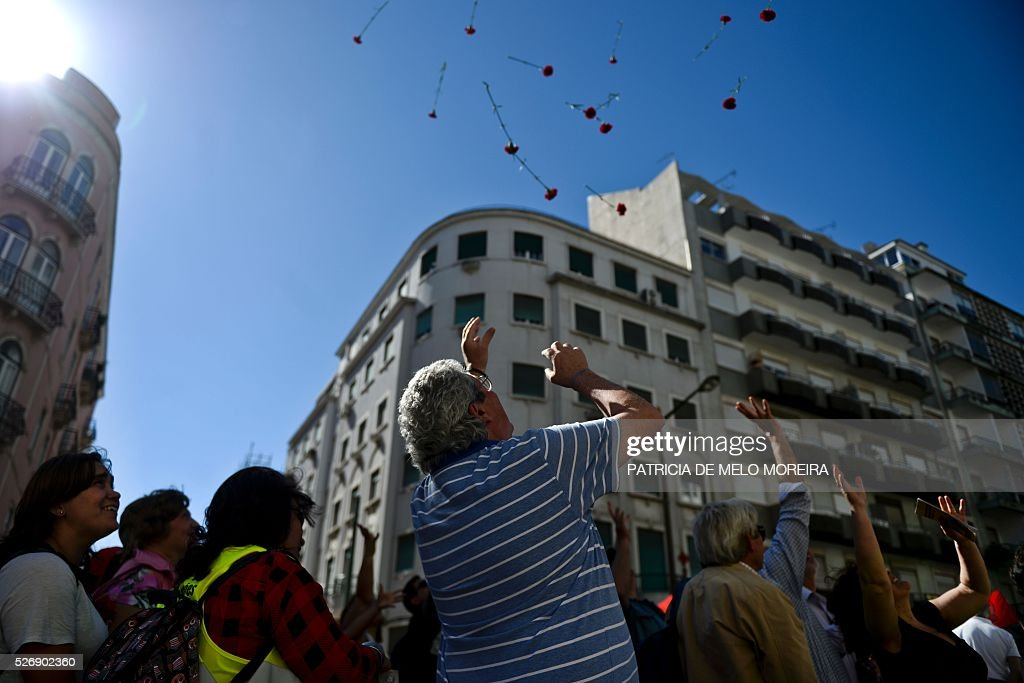 Demonstrators try to catch red carnations, symbol of the Portuguese revolution of 1974, thrown from buildings' windows during the traditional May Day rally in Lisbon on May 1, 2016. / AFP / PATRICIA