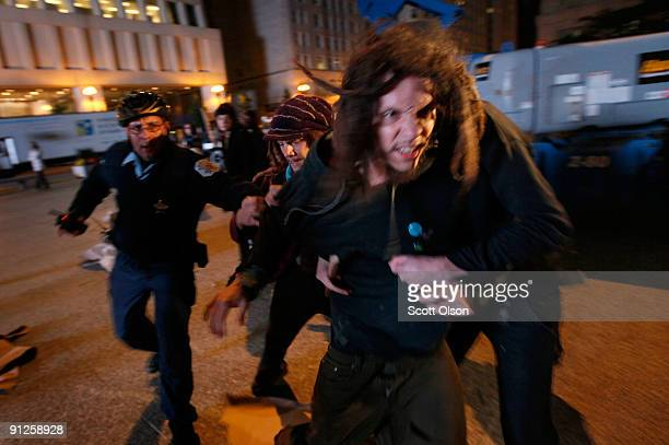 Demonstrators try to escape from police after interfering with city workers who were hanging an Olympic banner on the Picasso statue in Daley Plaza...