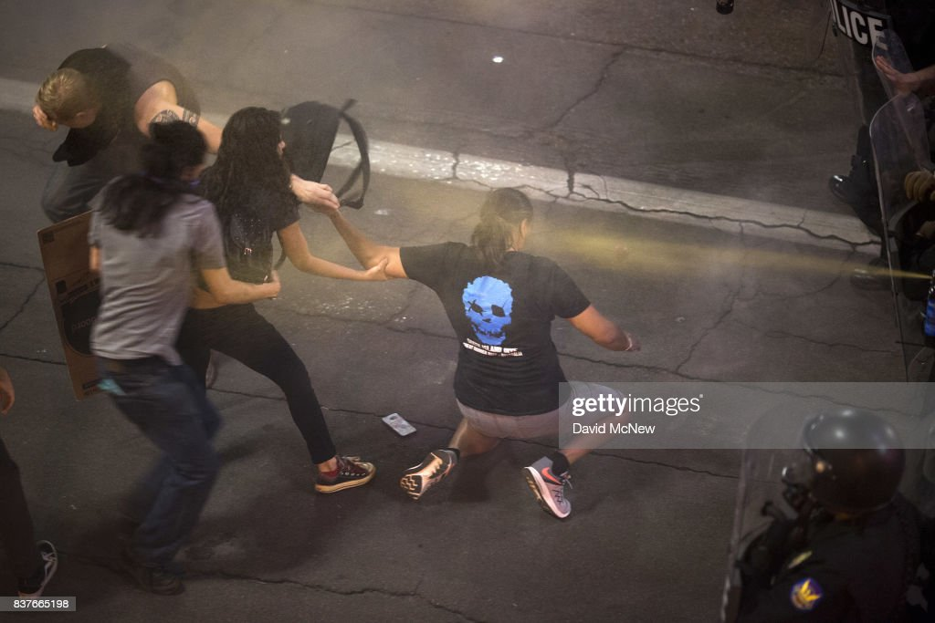 Demonstrators try to help a colleague as they are pepper sprayed repeatedly by advancing police officers after a rally by President Donald Trump at the Phoenix Convention Center on August 22, 2017 in Phoenix, Arizona. An earlier statement by the president that he was considering a pardon for Joe Arpaio, the former sheriff of Maricopa County who was convicted of criminal contempt of court for defying a court order in a case involving racial profiling, has angered Latinos and immigrant rights advocates.