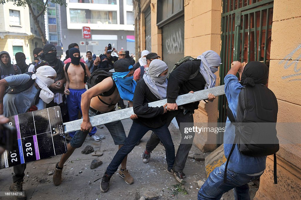 Demonstrators try to knock down the door of a house where there are policemen inside during a protest of students demanding to Chilean President Sebastian Pinera's government to improve the public education quality, in Santiago, on October 17, 2013. AFP PHOTO/Hector RETAMAL