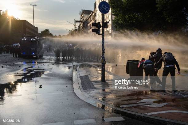 Demonstrators try to protect themselves behind a garbage can for the police water cannon during a demonstration against the G20 Summit on July 7 2017...