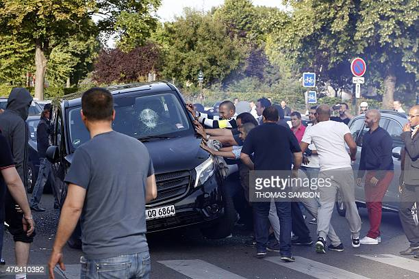 Demonstrators try to turn over an alleged minicab known in France as VTC at Porte Maillot in Paris on June 25 as hundreds of taxi drivers converged...