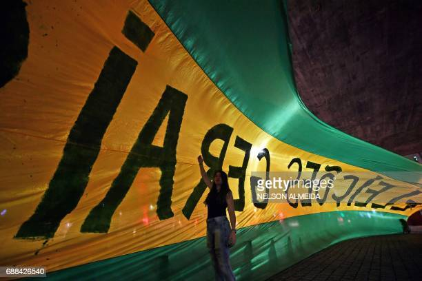 TOPSHOT Demonstrators unfurl a huge flag reading 'General elections now' during a protest against the government of president Michel Temer and to...